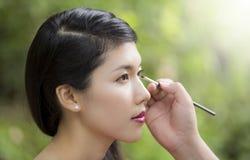 Make-upkünstler, der hellen niedrige Farblidschatten anwendet Lizenzfreie Stockfotografie
