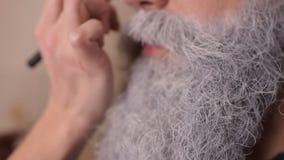 Make-upkünstler malt einen Mann ` s Bart stock video footage