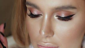 Make-upkünstler stellt Make-upwimpern in einer jungen Frau her stock video footage