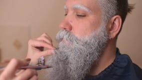Make-upkünstler tut Make-up einen Mann mit einem grauen Bart an stock footage