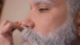 Make-upkünstler tut Make-up einen Mann mit einem grauen Bart an stock video footage