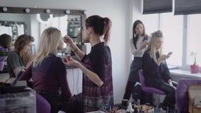 Make-upkünstler und Friseur des berühmten Kosmetiksalons arbeiten mit zwei Modellen, die für zukünftiges Schießen sich vorbereite stock video