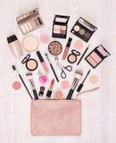 Make-upkosmetik und Zusätze und eine offene Tasche auf weißem hölzernem Hintergrund, Draufsicht stockfotografie