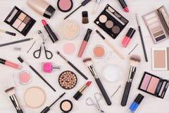 Make-upkosmetik wie Lidschatten, Lippenstift, Wimperntusche und Make-upzusätze auf weißem, hölzernem Hintergrund, Draufsicht stockfotos