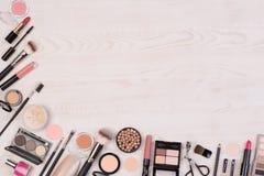 Make-upkosmetik wie Lidschatten, Lippenstift, Wimperntusche und Make-upzusätze auf weißem, hölzernem Hintergrund, Draufsicht mit  stockfotos