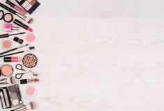 Make-upkosmetik wie Lidschatten, Lippenstift, Wimperntusche und Make-upzusätze auf weißem, hölzernem Hintergrund, Draufsicht mit  lizenzfreie stockfotografie