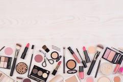 Make-upkosmetik wie Lidschatten, Lippenstift, Wimperntusche und Make-upzusätze auf weißem, hölzernem Hintergrund, Draufsicht mit  stockfotografie