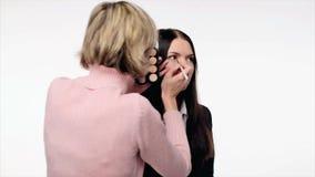 Make-upkunstenaar die de make-up van het model controleren stock videobeelden