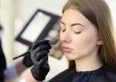 Make-upkunstenaar die de toon van de stichting toepast die speciale borstel op gezichts jong mooi model gebruikt De gezichtszorg  royalty-vrije stock afbeelding