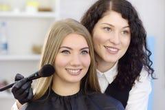 Make-upkunstenaar die de toon van de stichting toepast die speciale borstel op gezichts jong mooi model gebruikt De gezichtszorg  royalty-vrije stock foto
