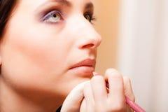 Make-upkunstenaar die met potloodschoonheidsmiddel van toepassing zijn op lippen van vrouw Stock Fotografie