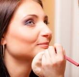 Make-upkunstenaar die schoonheidsmiddel op lippenvrouw toepassen Royalty-vrije Stock Foto