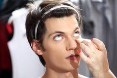 Make-upkunstenaar die stichting met een spons, mens in dres toepassen Royalty-vrije Stock Afbeelding