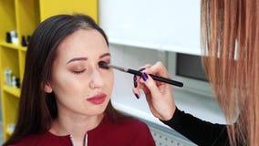 Make-upkunstenaar die make-upogen doen aan aantrekkelijke vrouw Manier en schoonheids de industrie stock video