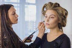 Make-upkunstenaar die vloeibare toon- stichting op het gezicht van de vrouw toepassen stock afbeeldingen