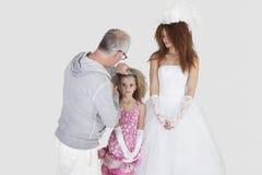 Make-upkunstenaar met het bespuiten op het haar van het bruidsmeisje terwijl bruid die over grijze achtergrond kijken Royalty-vrije Stock Afbeeldingen
