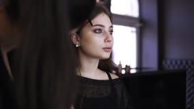 Make-upkunstenaar met lange poneystaart in het werk proces - verbetert de wenkbrauwlijn met een bruin potlood Zachte nadruk sluit stock video