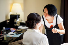 Make-upkunstenaar op het werk, Aziatische vrouw die make-up voor bruid, in ochtend doen Huwelijkskleding en schoenen stock foto's