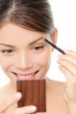 Make-upmädchen, das Augenbrauenfarbe in Spiegel einsetzt Stockbilder