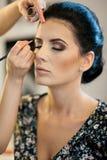 Make-upsitzung mit schöner junger Brunettefrau Maskenbildner, der die Augenbrauen einer attraktiven Dame des dunklen Haares tut lizenzfreie stockfotos