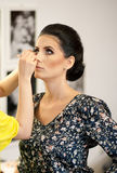 Make-upsitzung mit schöner junger Brunettefrau Maskenbildner, der die Augenbrauen einer attraktiven Dame des dunklen Haares tut stockfotografie