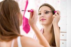 Make-upvrouw die lippenstift zetten die haarrollen dragen die klaar worden Royalty-vrije Stock Foto's