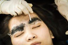 Make-upwenkbrauw die, vrij Aziatisch vrouwengezicht tatoeëren Stock Foto's