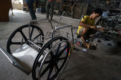 Make wheelchairs. Technicians are making wheelchairs for the disabled in a workshop in the city of Solo, Central Java, Indonesia Stock Photography
