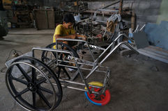 Make wheelchairs. Technicians are making wheelchairs for the disabled in a workshop in the city of Solo, Central Java, Indonesia Royalty Free Stock Photos