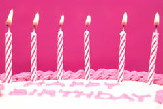 Make A Wish. Lit birthday candles on a pink cake are waiting to be blown out as a wish is being made Stock Images