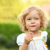 Make a wish. Little girl making a wish with spring flower stock images