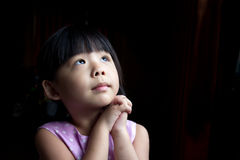 Make a wish. Little child is making a wish isolated in dark background Royalty Free Stock Photos