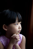 Make a wish. Little child is making a wish isolated in dark background Stock Photo