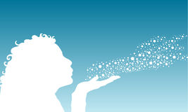Make a wish. Silhouette of a female blowing snowflakes Royalty Free Stock Image