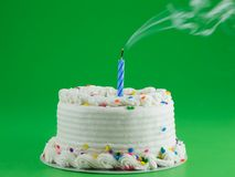 Make a wish. White frosted cake with a candle that has been blown out Stock Photos