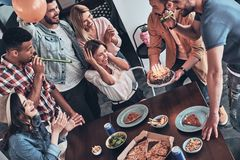 Make a wish!. Top view of happy people celebrating birthday among friends and smiling while having a dinner party royalty free stock photography
