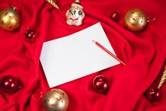A clean white sheet of paper and a red pencil lie on the blanket, and next to them are red and gold Christmas balls. Creative