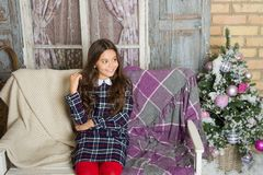 Make a wish. Small cute girl dreaming about christmas gift. Kid dreamy sit sofa dreaming about christmas present. Winter stock photography