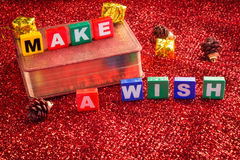 Make a wish. Wood box words on red fabric background stock photos