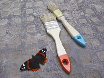 Make the world a more beautiful place. Red black butterfly and paintbrushes royalty free stock photo