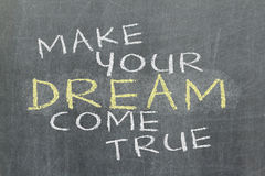 Make your dream come true - motivational slogan handwritten. With white chalk on blackboard Stock Images