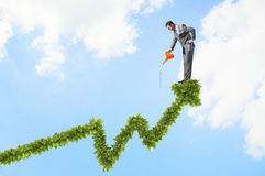 Make your income grow. Young cheerful businessman watering green growing graph with can Stock Photo