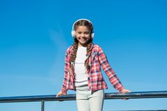 Make your kid happy with best rated kids headphones available right now. Girl child listen music outdoors with modern. Headphones. Enjoy sound. Kids headphones royalty free stock image