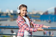 Make your kid happy with best rated kids headphones available right now. Girl child listen music outdoors with modern. Headphones. Kids headphones tested and stock photography