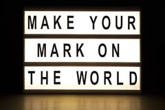 Make your mark on the world light box sign board. On wooden table royalty free stock photo