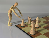 Make Your Move!. Wooden mannequin moving chess pieces Royalty Free Stock Photos