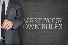 Make your own rules on blackboard with businessman Stock Photo