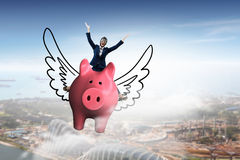 Make your savings work for you . Mixed media . Mixed media. Young cheerful businesswoman flying on pink piggy bank. Mixed media Royalty Free Stock Photo