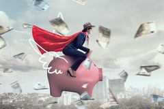 Make your savings work for you . Mixed media. Young businesswoman riding on piggy bank presenting banking and saving concept Royalty Free Stock Photo