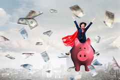 Make your savings work for you . Mixed media. Young cheerful businesswoman flying on pink piggy bank. Mixed media Royalty Free Stock Photo